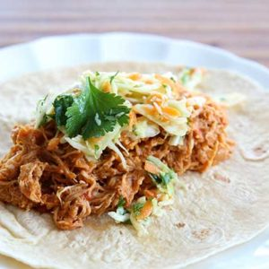 Crock pot Chicken Fajitas served on tortilla topped with Mexican Coleslaw and cilantro in a white plate