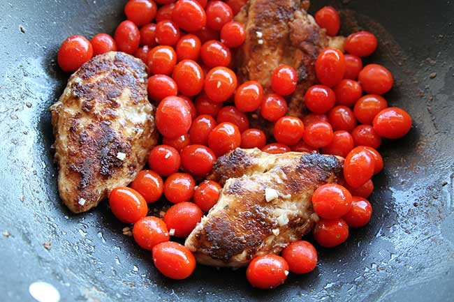 chicken breast dredged through spices and flour in a skillet with oil and butter and tomatoes