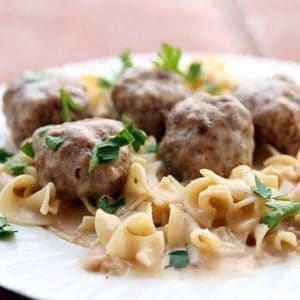 Close up Turkey Swedish Meatballs served over egg noodles garnished with parsley leaves