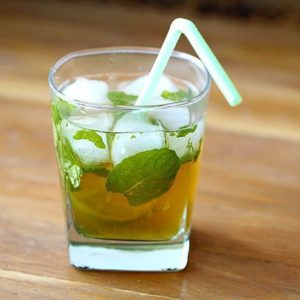 Maple Whiskey Mojito in a whisky glass with mint leaves and slice of lime on wood background