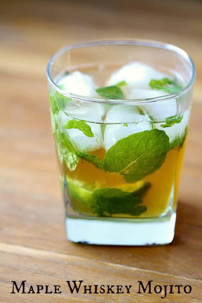 Close up of Maple Whiskey Mojito in a whisky glass with ice, mint leaves and slice of lime