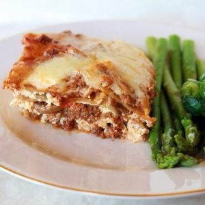 close up of Cheesy Beef Lasagna in a white plate with Brussels sprouts and asparagus