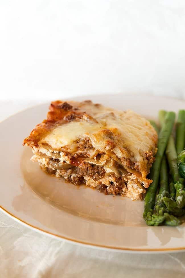 cheesy beef lasagna on a white plate with asparagus
