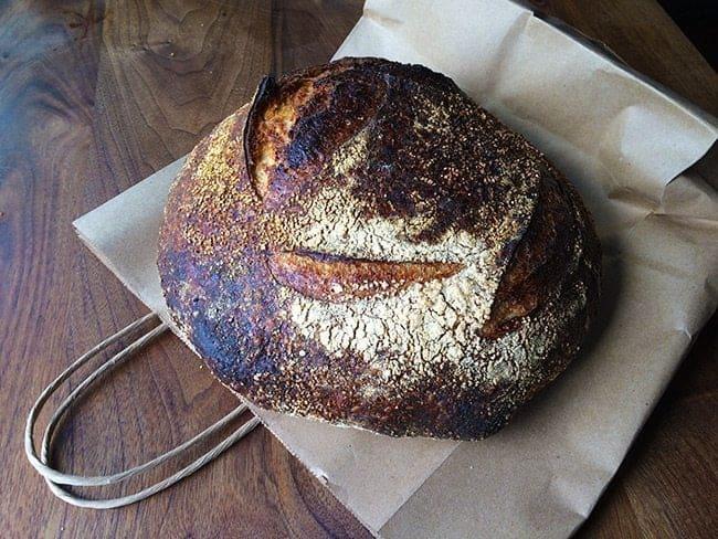 loaf of the Polenta Porridge Bread over a paper bag