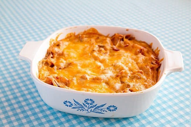 White Bean Ranch, Bacon & Cheddar Dip in a white casserole dish on a blue printed tablecloth