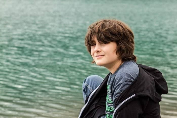 young boy wearing shirt and black jacket near the sea
