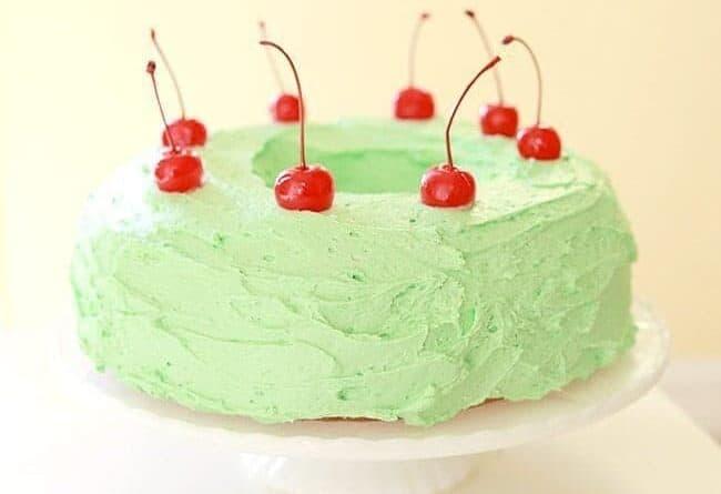 Watergate Salad Cake Garnish with Cherries on a White Cake Holder