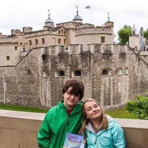 kids picture holding a book with the background of Tower of London