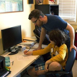 young boy with his dad in the study room
