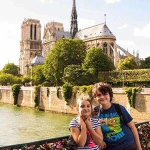 kids at standing at Love Locks Bridge in Paris