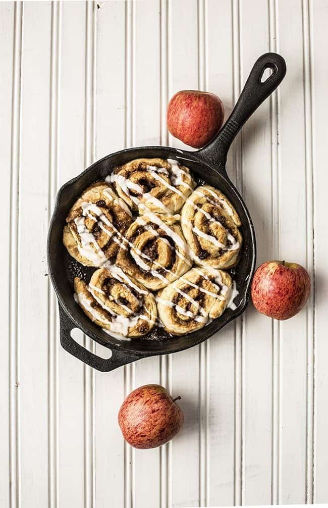 top down shot of 6 pieces Glazed Apple Pie Cinnamon Buns in Skillet with 3 fresh apples on white background