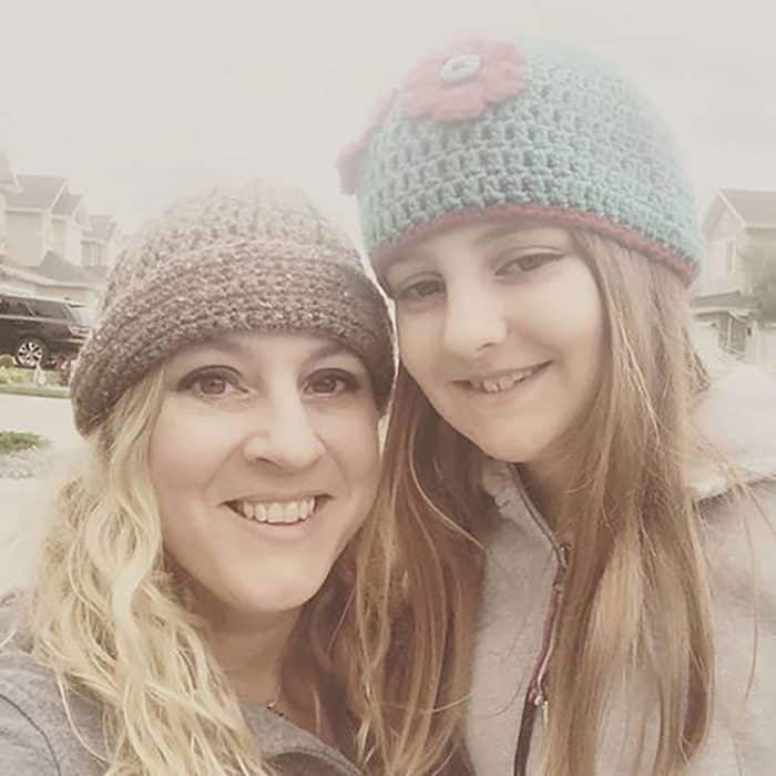 smiling mother and daughter with long hair wearing beanie hat