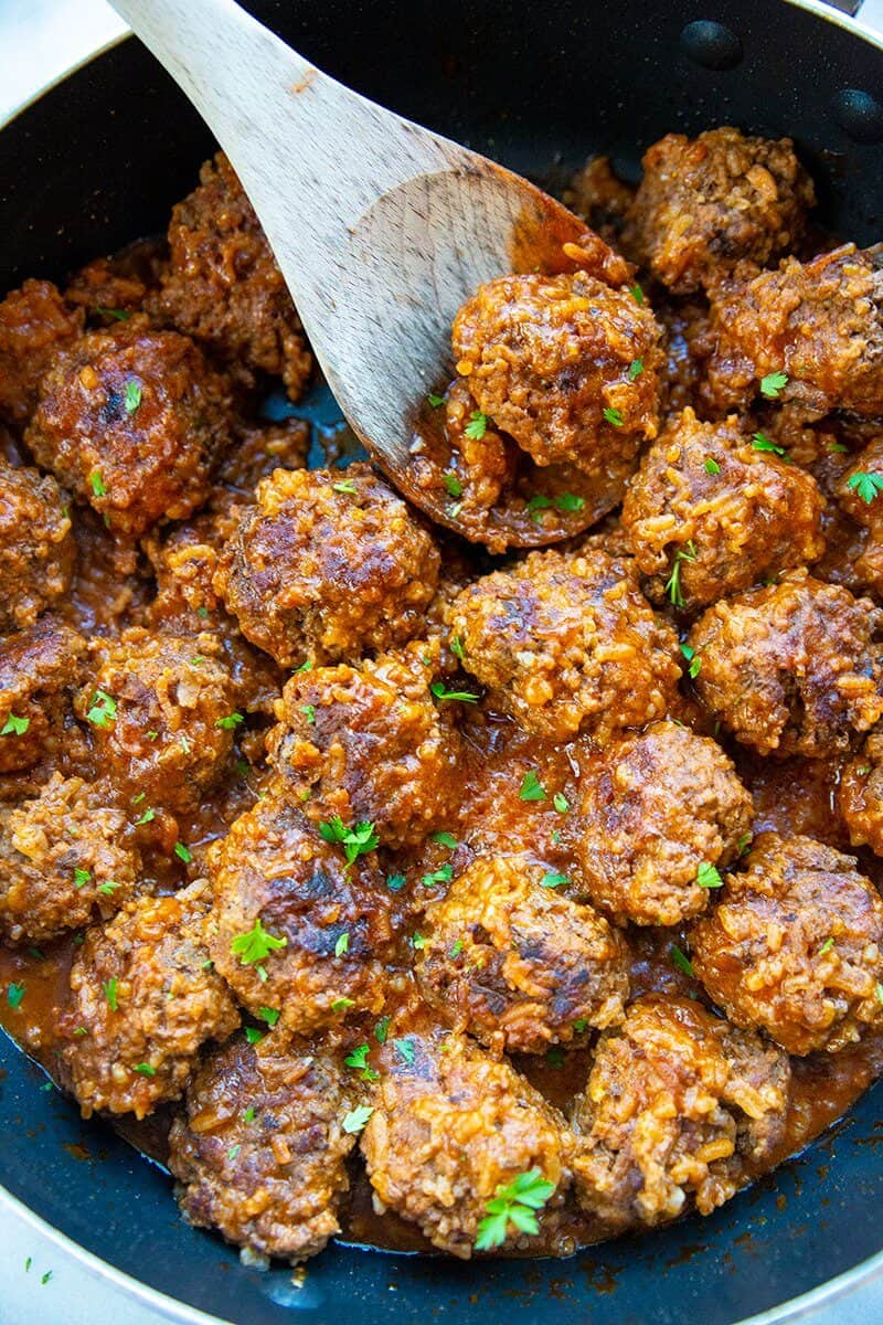 close up porcupine meatballs in a large black skillet with a wooden spoon and some teared parsley leaves