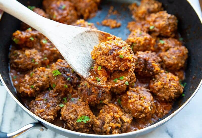 porcupine meatballs in a large black skillet with a wooden spoon and some teared parsley leaves