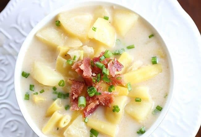 Creamy Yellow Bean & Potato Soup in a white bowl, topped with green onions and bacon