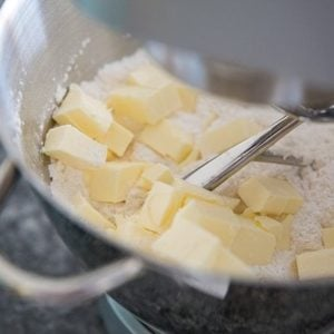 slices of butter in a mixing bowl together with flour and other ingredients for Christmas Cherry Scones