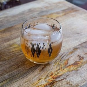 The Log Cabin Cocktail in a retro shot glass on a wood background