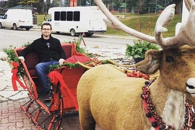 man sitting in the Christmas reindeer cart