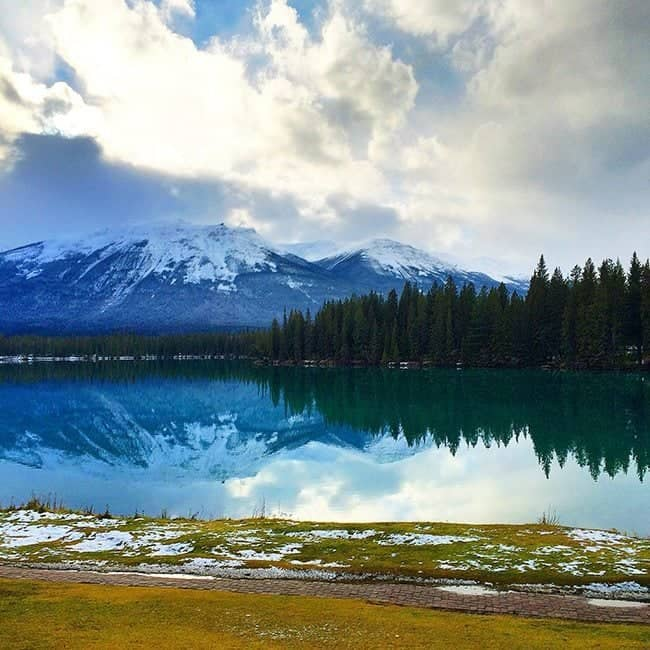 glorious scenery of a lake with reflection of mountain with snow