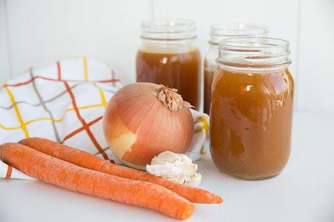 Crock Pot Bone Broth on Jars, Organic Carrots and Onion in kitchen cloth beside it