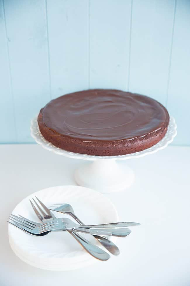 Flourless Chocolate Cake in a white cake stand, dessert plates and forks beside it