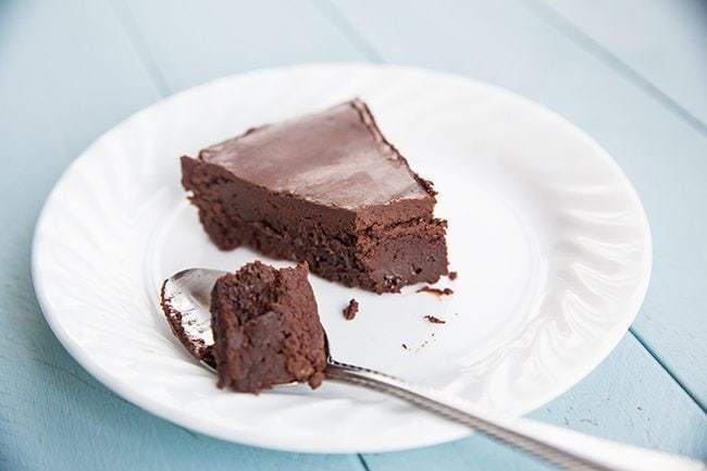 a spoon with Chocolate cake and a slice of Flourless Chocolate Cake in a white plate