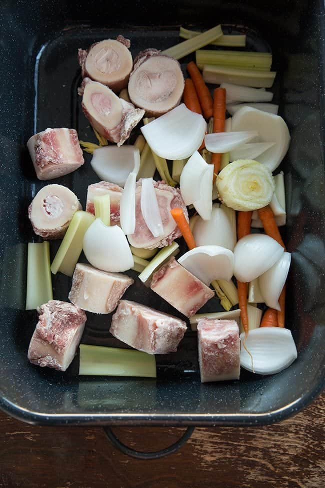 Bones and chopped vegetables in Crockpot ready for roasting