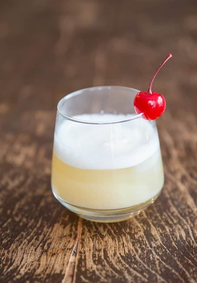A glass of Smoky Whisky Sour with egg white on top and Garnish with Cherry on Wood background