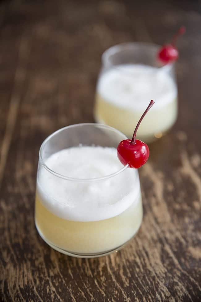 Close up of Two glasses of Smoky Whisky Sour Garnish with Cherry on Wood background