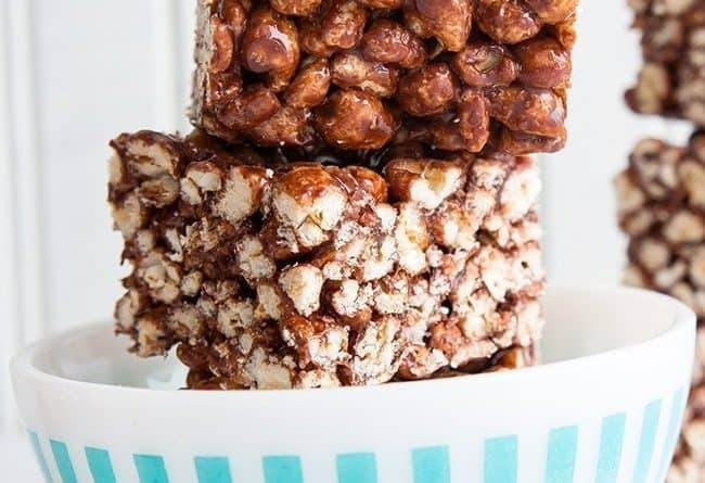 Close up of Stacks of Chewy Chocolate Puffed Wheat Squares in White Bowl on White Background