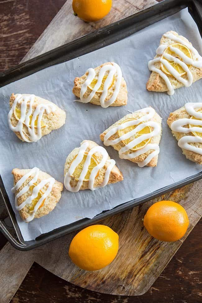 Top down shot of Meyer Lemon Scones Glazed with Icing in baking sheet with parchment paper, some fresh lemon fruits around