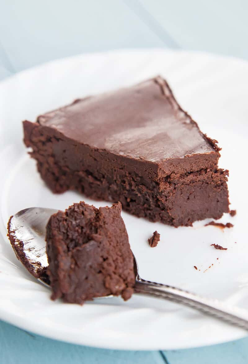 close up slice of Flourless Chocolate Cake in a white plate