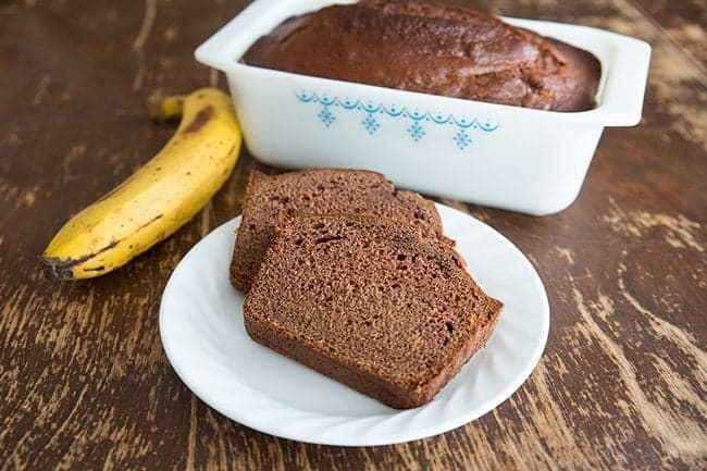 Slices of Chocolate Banana Bread in White plate and a loaf in baking pan, ripe yellow banana on side