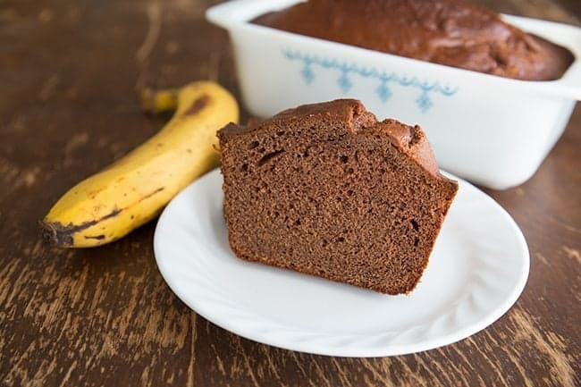 Close up of  Chocolate Banana Bread Slice in White plate and a loaf in baking pan, ripe yellow banana on side