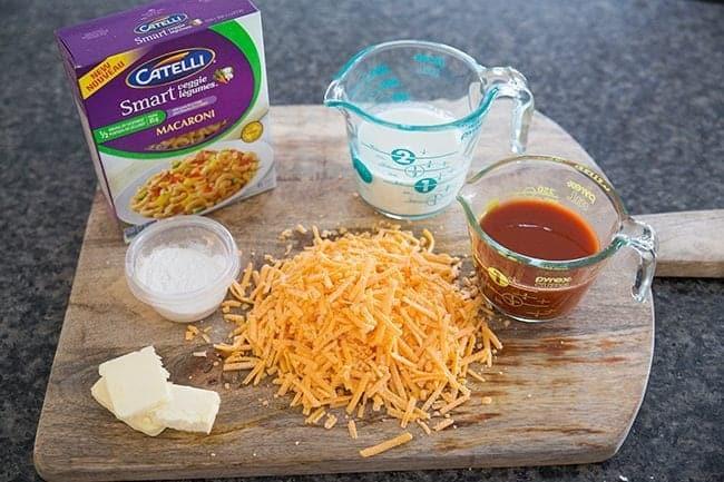 Ingredients needed in making Sneaky Vegetable Mac n' Cheese all in wooden board