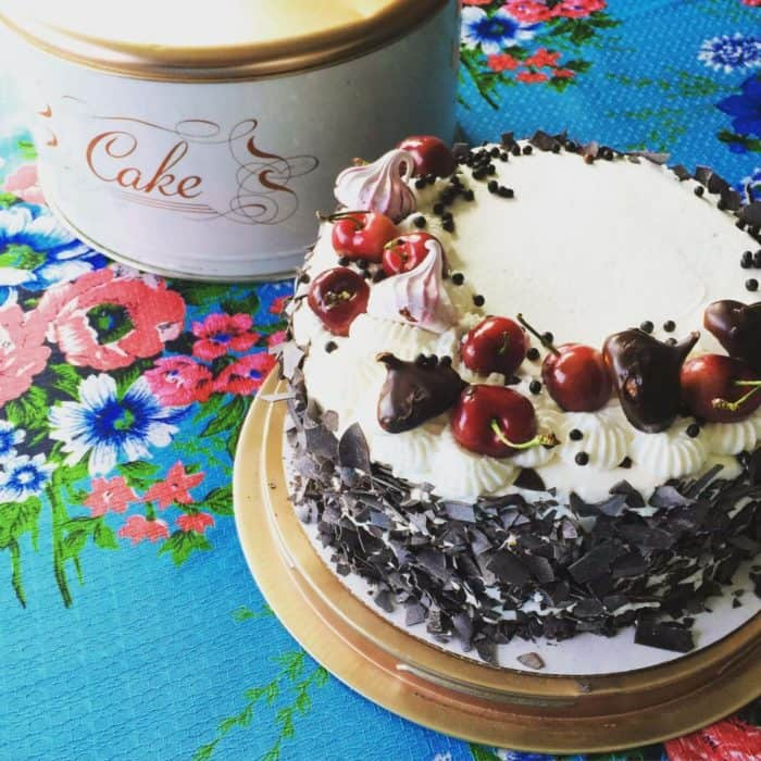 Black Forest Cake in a gold cake holder and a cake can on the background