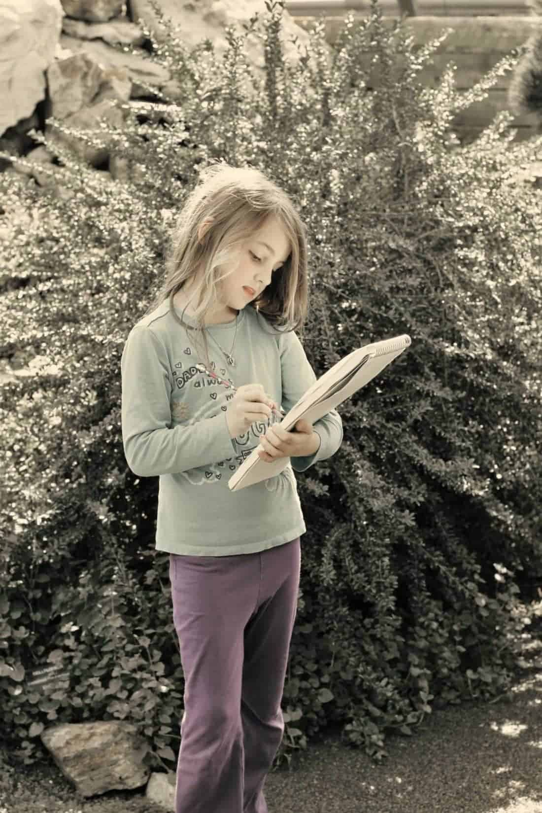little girl standing, holding her sketchpad and pencil in the garden