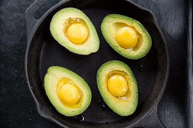 Eggs cracked in each half of avocados