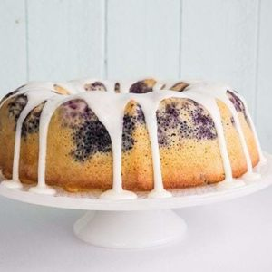 Blueberry Lime Bundt Cake on white cake holder drizzle with lime glaze
