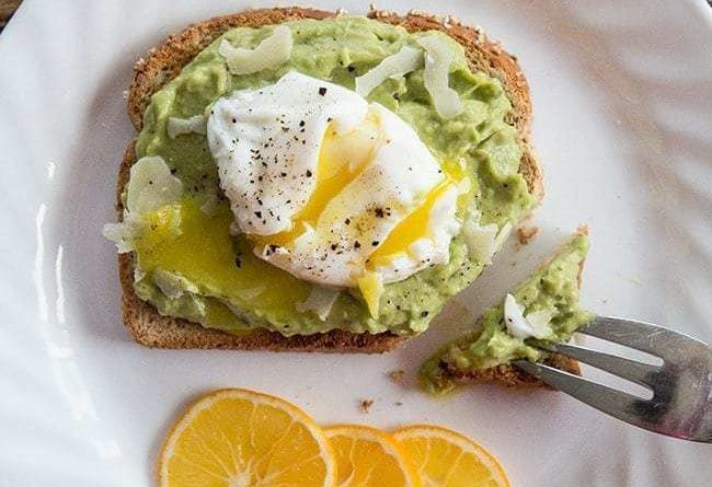 white plate with 3 lemon slices, an avocado toast and egg with Parmesan cheese