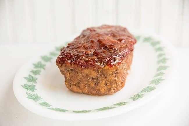 white plate with baked Meatloaf topped with sauce on white background
