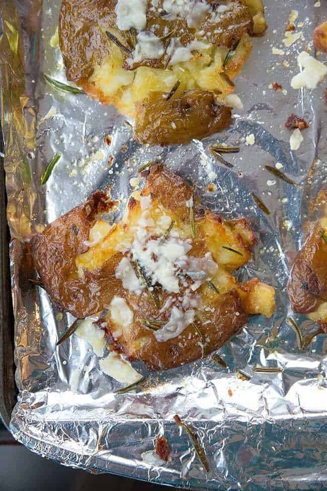 flat smashed potatoes with skin crisped up in a large baking sheet lined with tin foil