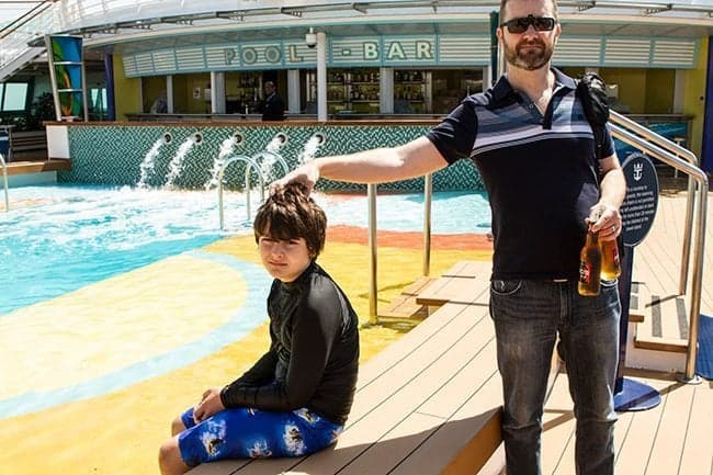 Son sitting while his Father holding 2 drinks in front of Royal Caribbean's Brilliance of the Seas Pool Bar
