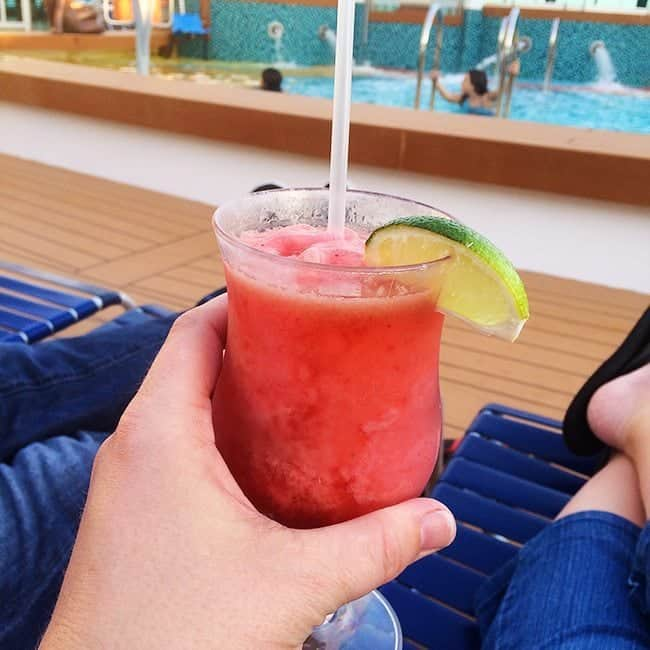 holding a glass of strawberry daiquiri with a slice of lime