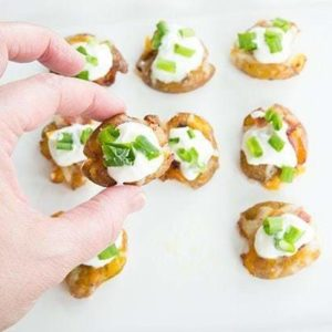 top down shot of Mini Loaded Smashed Potato Bites topped with sour cream, bacon, cheese and green onions