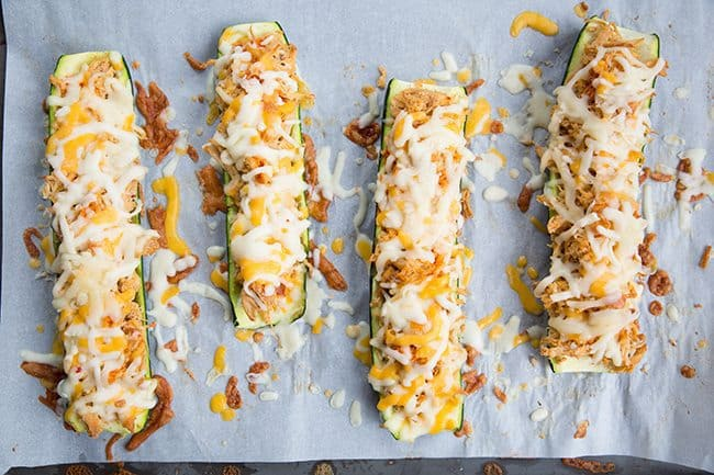 Cheesy Buffalo Chicken Zucchini Boats in a baking sheet with parchment paper