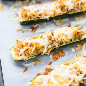 close up Cheesy Buffalo Chicken Zucchini Boats in a baking sheet lined with parchment paper