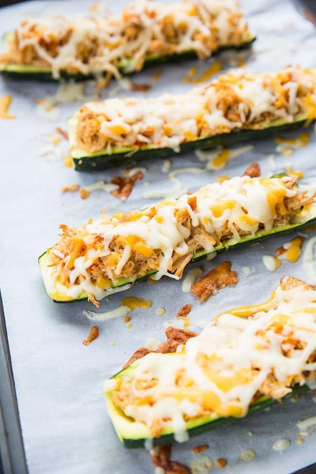 4 pieces of Cheesy Buffalo Chicken Zucchini Boats in a baking sheet lined with parchment paper