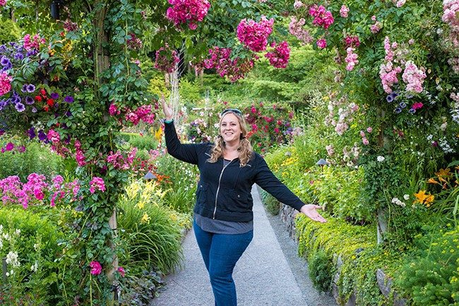 woman standing in the middle of the pathway full of flowers on both sides