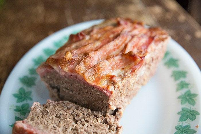 Sliced Bacon Topped Mozza Meatloaf in White Plate with Green Leaves Prints